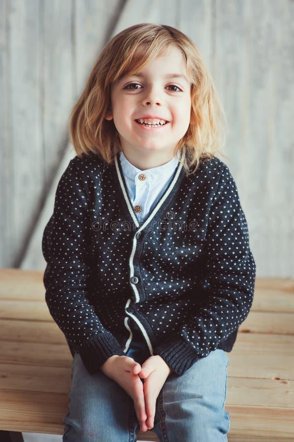 Innenporträt von 5 Jahren alten Jungen mit dem langen Haar, das auf Tabelle sitzt stockbilder
