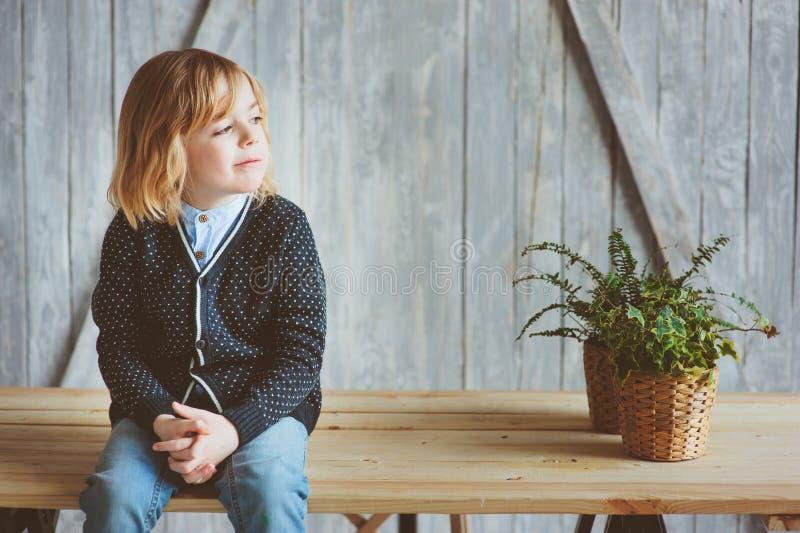 Innenporträt von 5 Jahren alten Jungen mit dem langen Haar, das auf Tabelle sitzt lizenzfreie stockfotografie