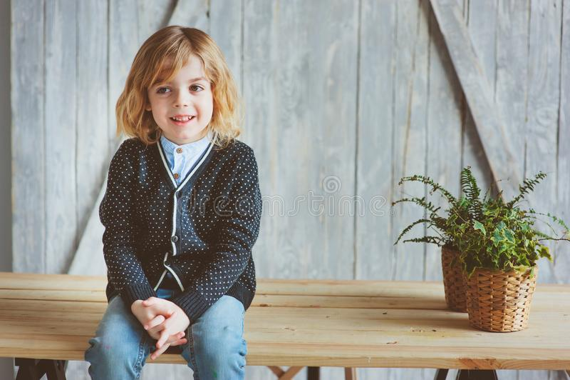Innenporträt von 5 Jahren alten Jungen mit dem langen Haar, das auf Tabelle sitzt stockfoto