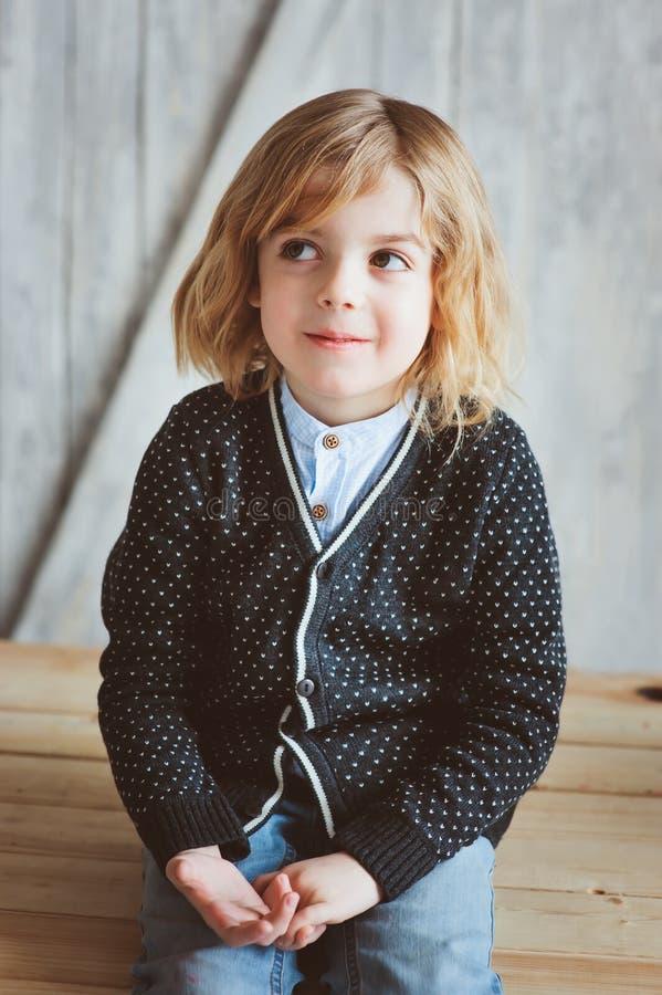 Innenporträt von 5 Jahren alten Jungen mit dem langen Haar, das auf Tabelle sitzt lizenzfreies stockbild