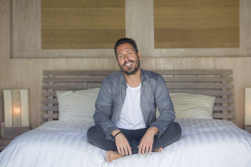 Innenporträt von 30s zu 40s, das glücklich ist und gut aussehender Mann zu Hause im zufälligen Hemd und in den Jeans, die auf Bet stockbild