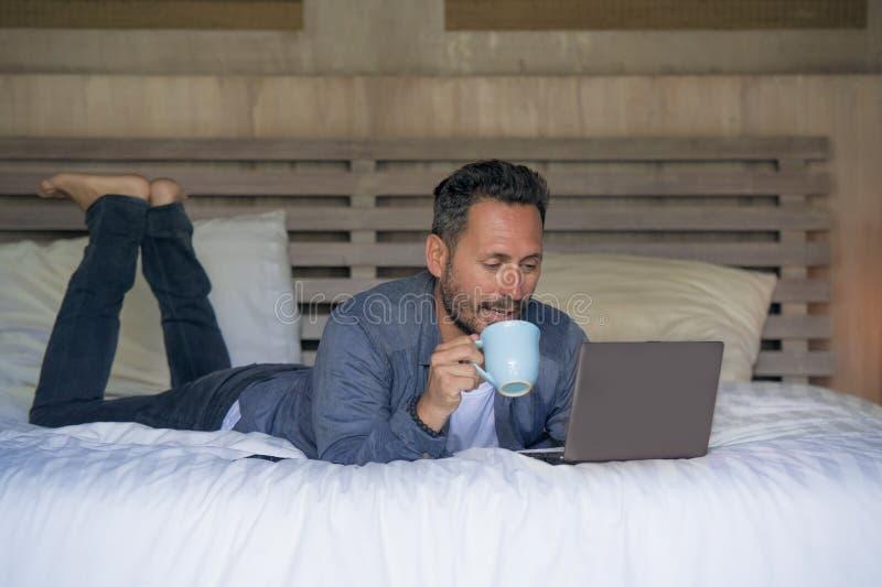 Innenportr?t des jungen attraktiven und gl?cklichen Arbeitens des Mannes zu Hause entspannt auf Bett mit Laptop-Computer herein l stockfotografie
