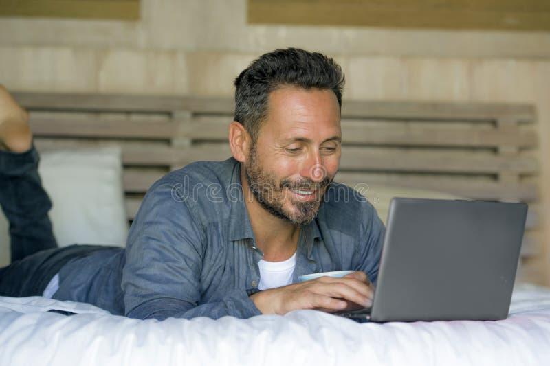 Innenportr?t des jungen attraktiven und gl?cklichen Arbeitens des Mannes zu Hause entspannt auf Bett mit Laptop-Computer herein l stockfoto