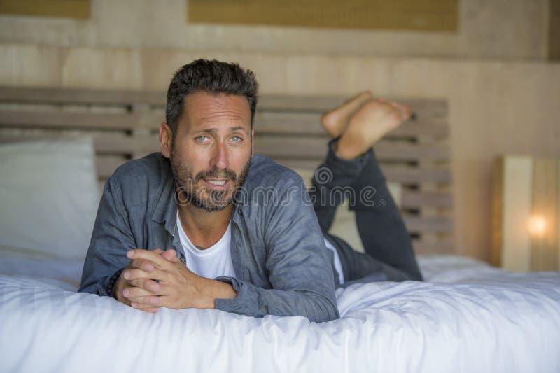 Innenportr?t von 30s zu 40s, das gl?cklich ist und gut aussehender Mann zu Hause im zuf?lligen Hemd und in den Jeans, die auf Bet lizenzfreie stockfotos