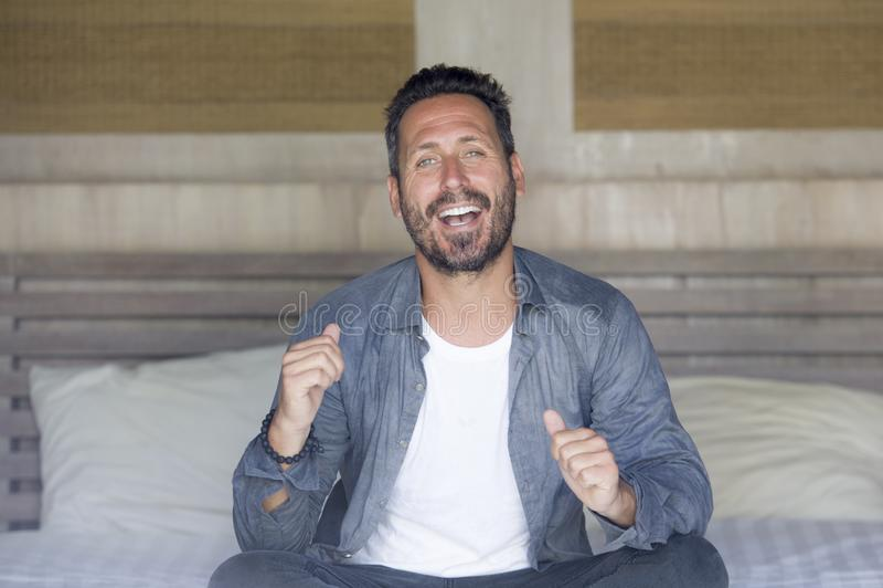 Innenportr?t von 30s zu 40s, das gl?cklich ist und gut aussehender Mann zu Hause im zuf?lligen Hemd und in den Jeans, die auf Bet lizenzfreie stockbilder