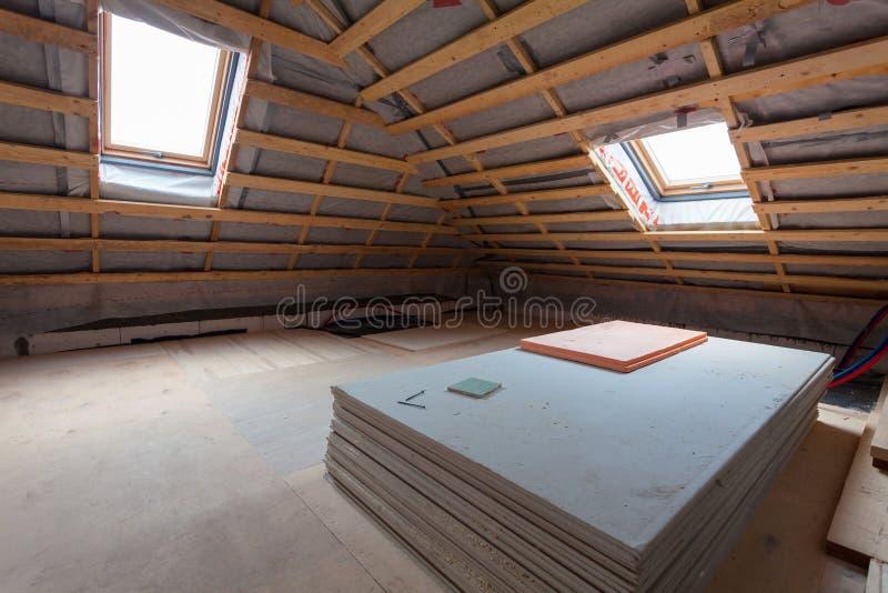 Innenraum der Raumwohnung mit neuen Fenstern und Materialstücken der Trockenmauer während auf der Erneuerung, der Überholung und  lizenzfreies stockbild