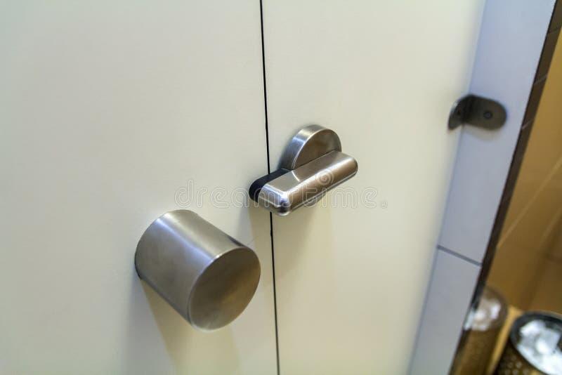 Innenraum der Toilettentoilette, weiße geschlossene Tür mit Verschluss und rostfreier Griff Privatleben- und Hygienekonzept stockfotos