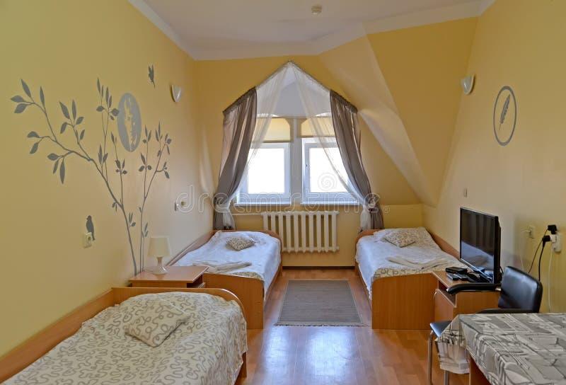 Innenraum des dreifachen Hotelzimmers mit einem Porträt des russischen Dichters Sergey Yesenin auf einer Wand lizenzfreie stockbilder