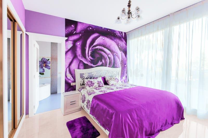 Innenraum des gemütlichen Schlafzimmers in den hellen violetten Tönen Großes widergespiegelt stockbild
