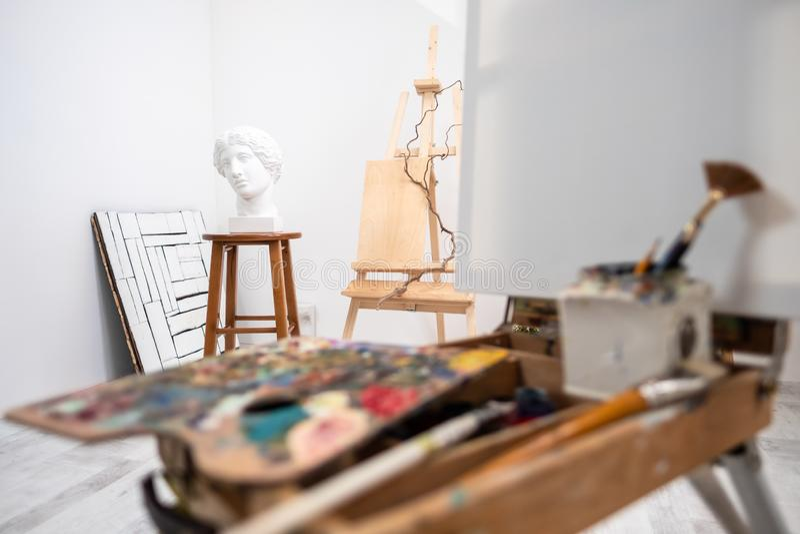 Innenraum des weißen Studios des Künstlers, kreative Person Gestell, Bürsten, Gipskopf und Zahlen Dachboden, hohe Decken lizenzfreie stockbilder