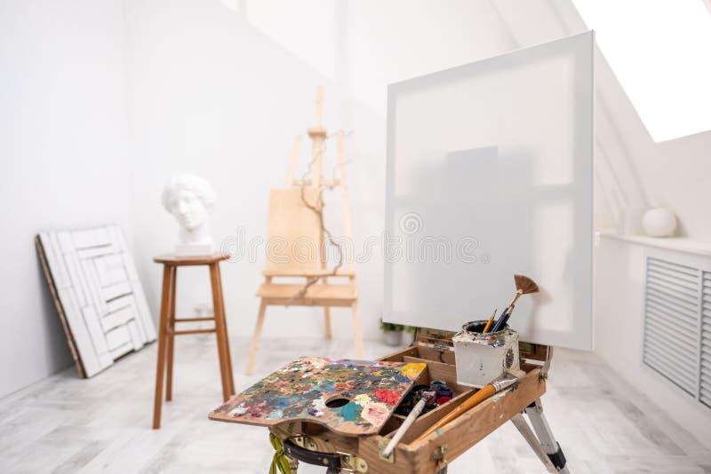 Innenraum des weißen Studios des Künstlers, kreative Person Gestell, Bürsten, Gipskopf und Zahlen Dachboden, hohe Decken stockbild