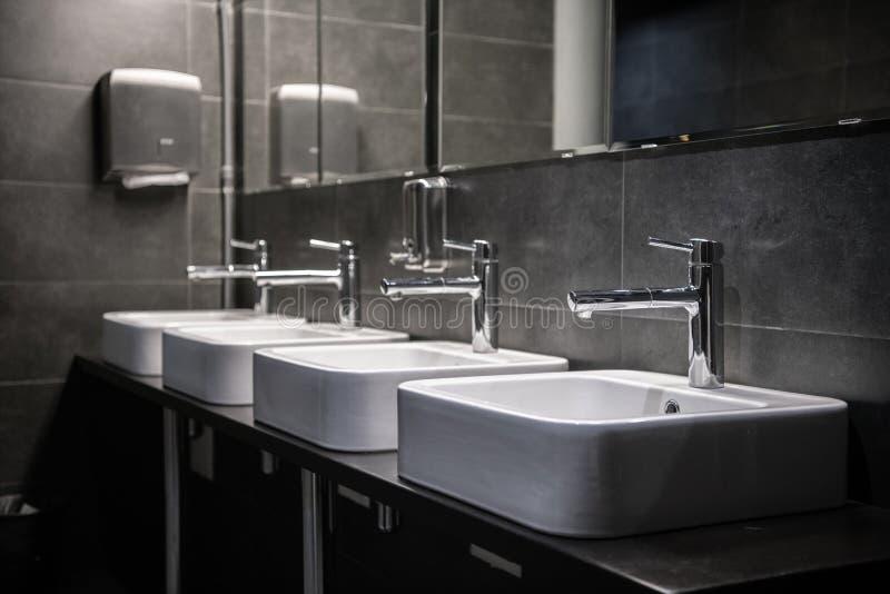 Innenraum einer modernen allgemeinen Badezimmertoilette in den grauen Farben stockfoto
