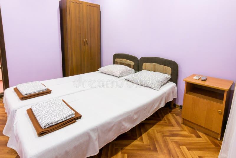 Innenraum eines kleinen Raumes mit einem Doppelbett, einem Nachttisch und Garderobe lizenzfreie stockfotografie