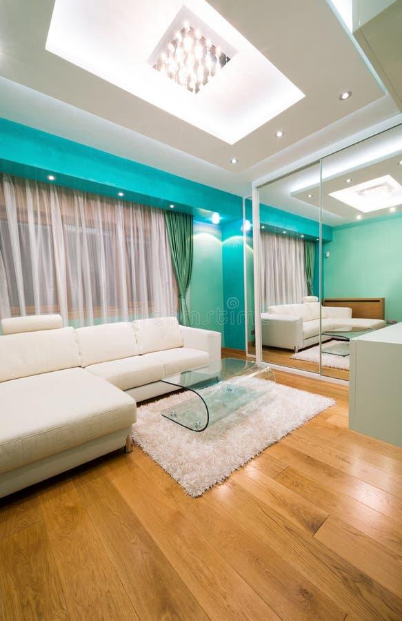Innenraum eines modernen grünen Wohnzimmers mit Luxusdeckenleuchte lizenzfreie stockbilder