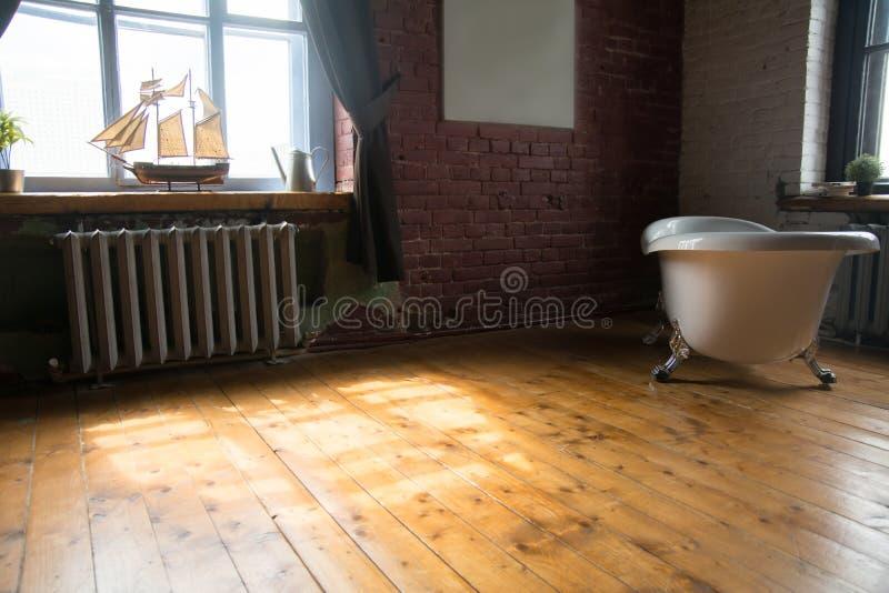 Innenraum eines Raumes mit einer schönen Luxusweinlesebadewanne auf einem Bretterboden und einem vorbildlichen Schiff stockfotos