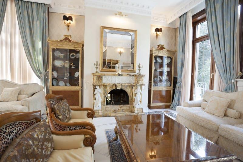 Innenraum eines Wohnzimmers mit Kamin im Luxuslandhaus lizenzfreie stockfotos