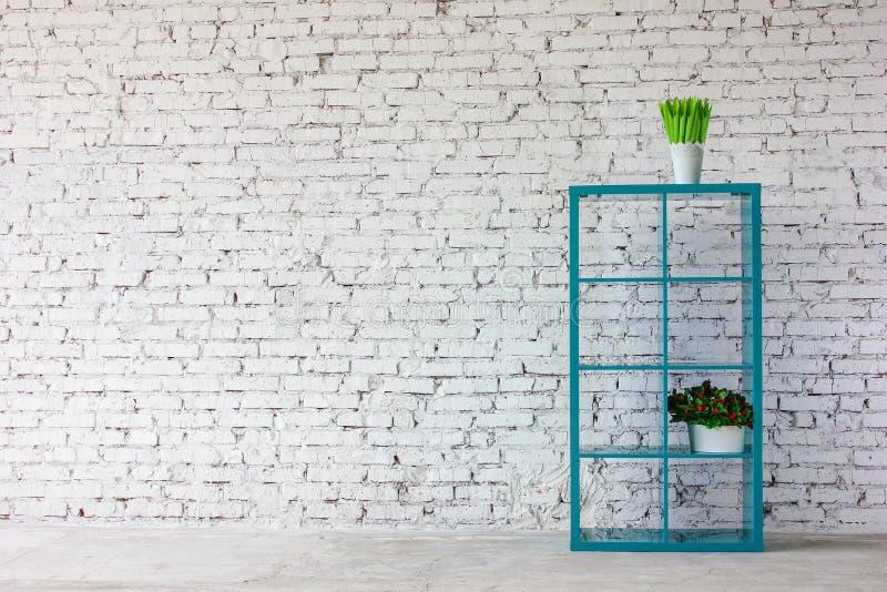 Innenraum im weißen Ziegelstein mit einem Bücherregal stockfotografie