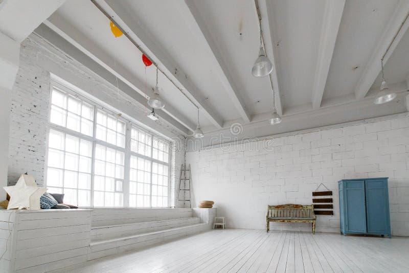 Innenraum mit Weinlesemöbeln, helles Studio mit alter Bank und blauer Kasten Geräumiges Studio mit einer hohen Decke und einem a stockfotos