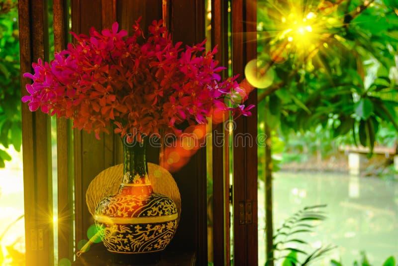 Innenraum, Orchideenbetriebsvasen mit schönen purpurroten Blüten mit Beleuchtungsaufflackerneffekt auf Fenster stockfoto