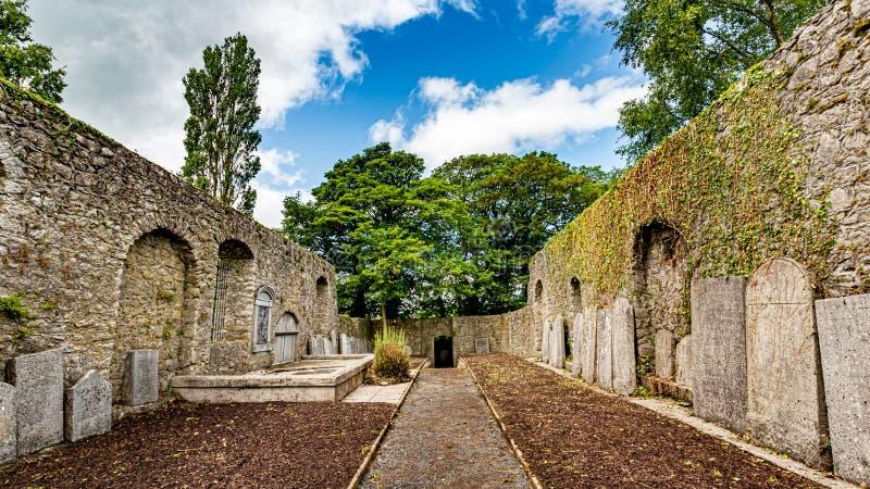 Innenraum von Abbey Graveyard mit einem Weg in der Mitte und Finanzanzeigen in der Stadt von Athlone stockbilder