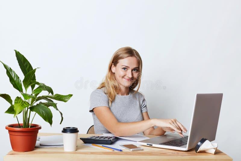 Innenschuß der attraktiven Geschäftsfrau mit glücklichem Ausdruck, setzend an der Laptop-Computer mit Monotype und sind mit der H lizenzfreie stockfotos