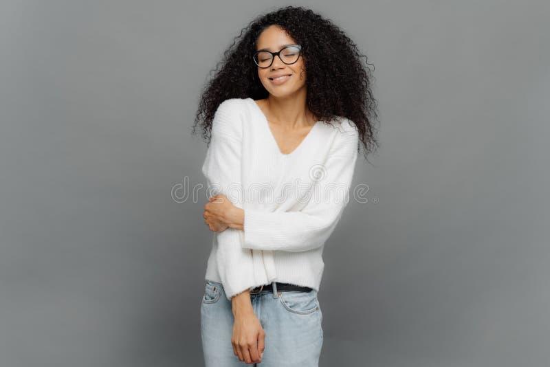 Innenschuß der aufrichtigen Frau hält Hand kreuzte teils, angekleidet im weißen Pullover und Jeans, hat die geschlossenen Augen,  lizenzfreies stockfoto