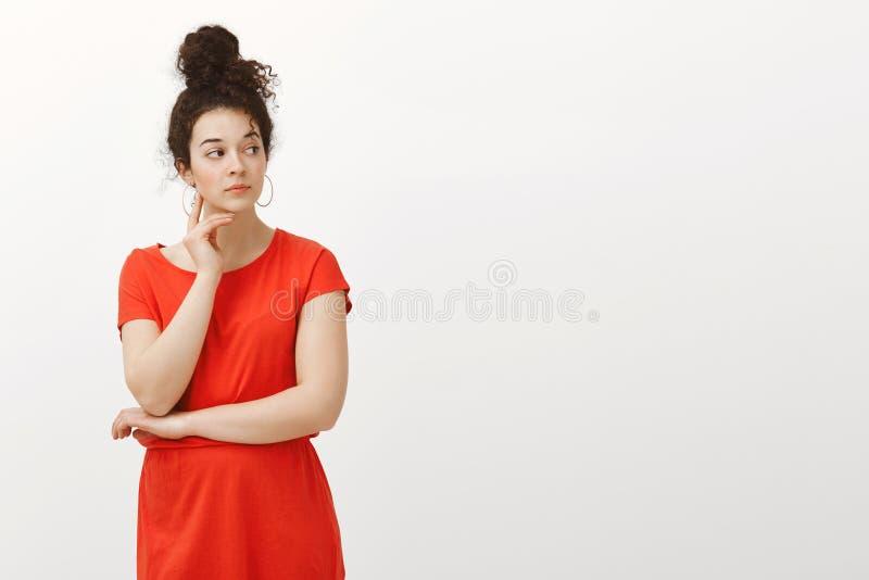Innenschuß der neugierigen ernsten Frau mit dem gelockten Haar gekämmt, im Brötchen, in tragendem rotem Kleid, in rührendem Gesic lizenzfreie stockfotos