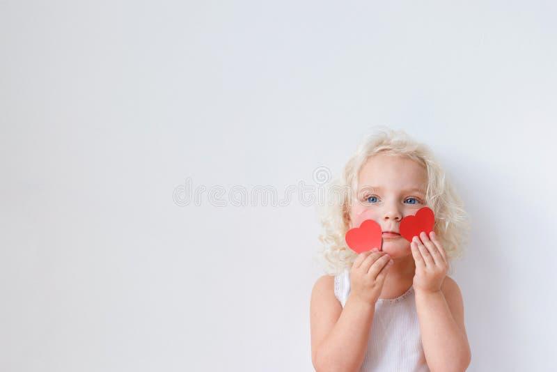 Innenschuß der recht blonden Frau mit blauen Augen, Griffe zwei rote Papierherzen, wirft gegen weißen Hintergrund mit Kopie auf lizenzfreie stockfotografie
