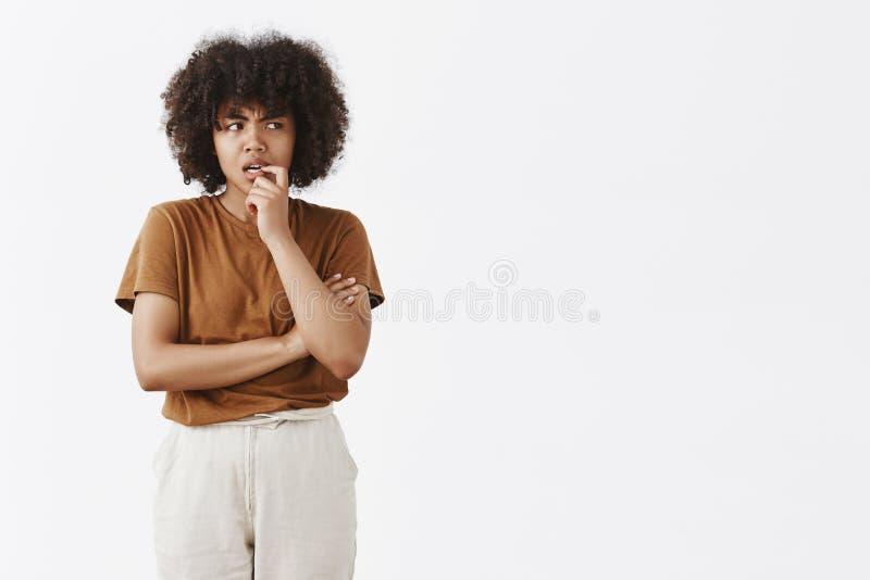 Innenschuß der zweifelhaften und gefragten thoghtful jungen Afroamerikanerfrau mit Afrofrisur im braunen T-Shirt lizenzfreie stockbilder