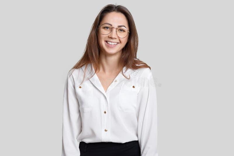 Innenschuß des angenehmen schauenden lächelnden jungen weiblichen Architekten trägt transparente runde Gläser, formale Ausstattun stockfotografie