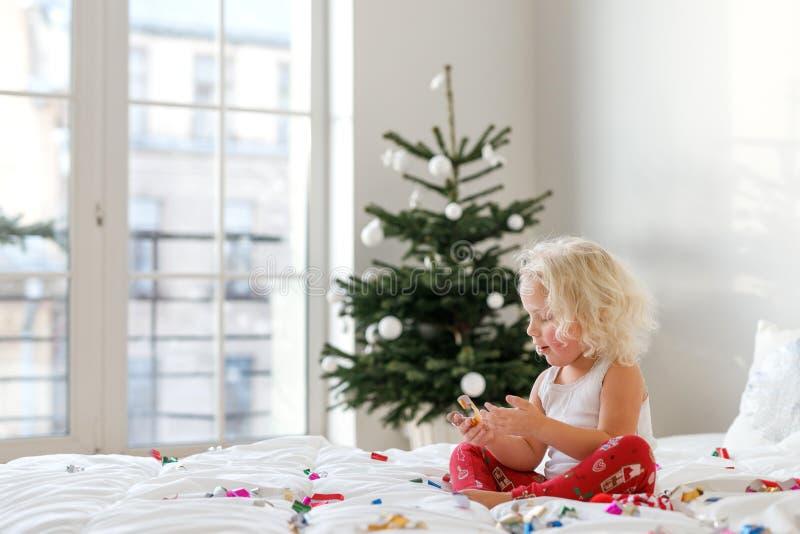Innenschuß des blonden gelockten Kleinkindes sitzt gekreuzte Beine auf bequemem Bett, Spiele mit bunten Papieren, verziertes neue stockbild