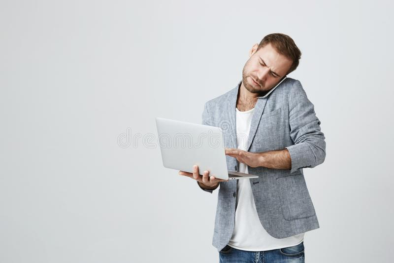 Innenschuß des erfolgreichen jungen kaukasischen Managers mit der Stoppel, die gegen grauen Hintergrund mit dem offenen Laptop ha stockbild