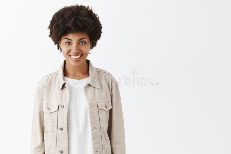 Innenschuß des netten Wildfangmädchens mit dunkler Haut und der Afrofrisur in der modischen beige Jacke über T-Shirt, breit läche lizenzfreies stockfoto