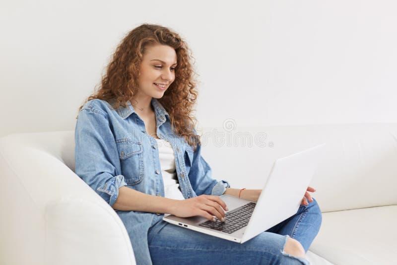 Innenschuß des positiven attraktiven Mädchens mit dem gelockten Haar plaudernd mit ihren Freunden an den Social Networking-Stando lizenzfreie stockfotografie