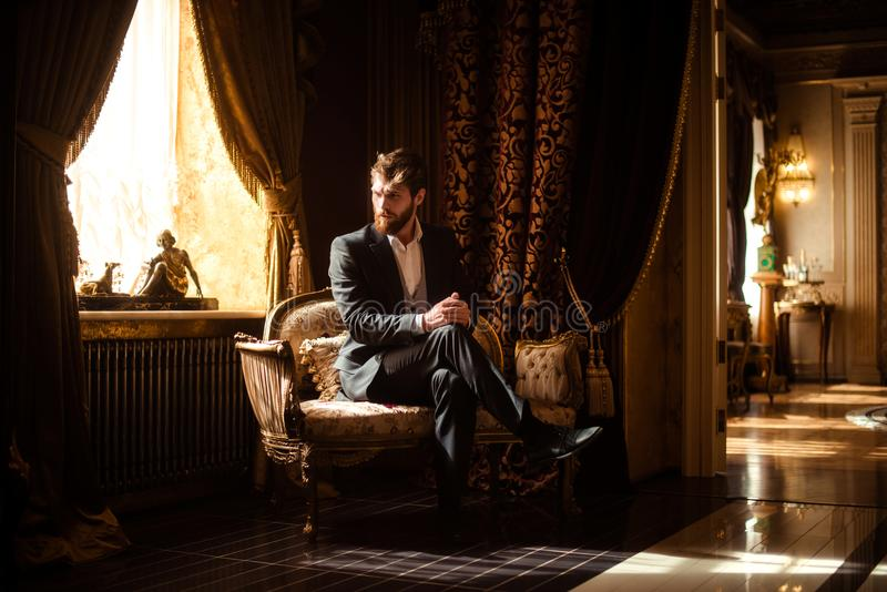 Innenschuß des wohlhabenden intelligenten ernsten Geschäftsmannes sitzt auf bequemem Sofa im reichen Raum mit Luxusmöbeln stockbilder