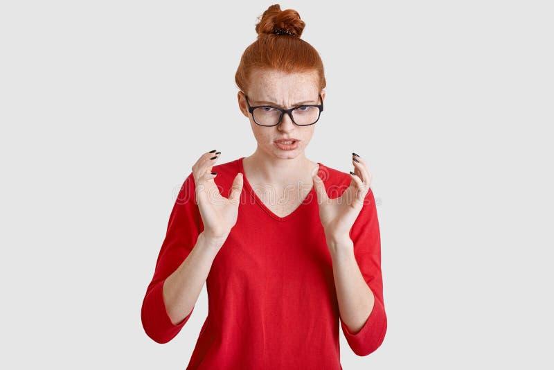 Innenschuß von empörten Frauengesten verärgert, hat die Stirn gerunzelten Ausdruck, trägt Schauspiele und rote Kleidung, schaut m stockfoto