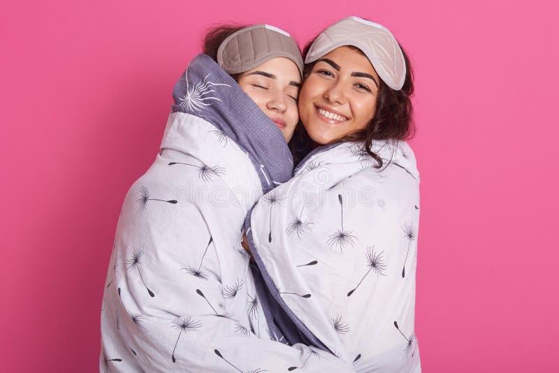 Innenschuß von lächelnden Frauen mit Schlafmasken, tragende umfassende Stände, die über rosafarbenem Studiohintergrund, Pyjamas h lizenzfreie stockbilder