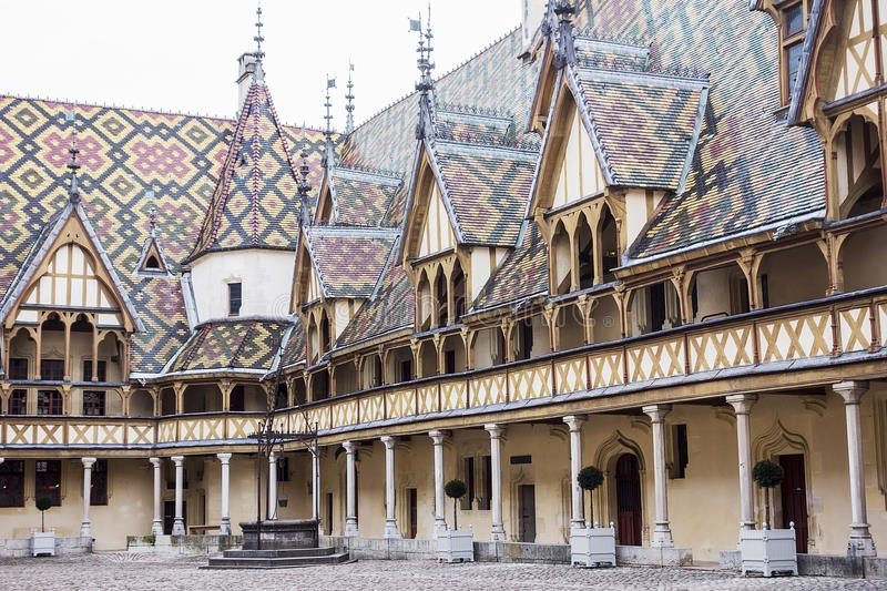 Inner Courtyard At Hospices de Beaune. The inner courtyard at the Hospices de Beaune features a well and an ornate decorated roof with patterns made from yellow stock photo