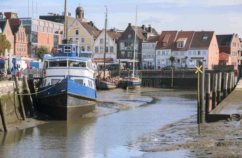 Inner harbor at low tide in the old town of Husum with boats on stock photography