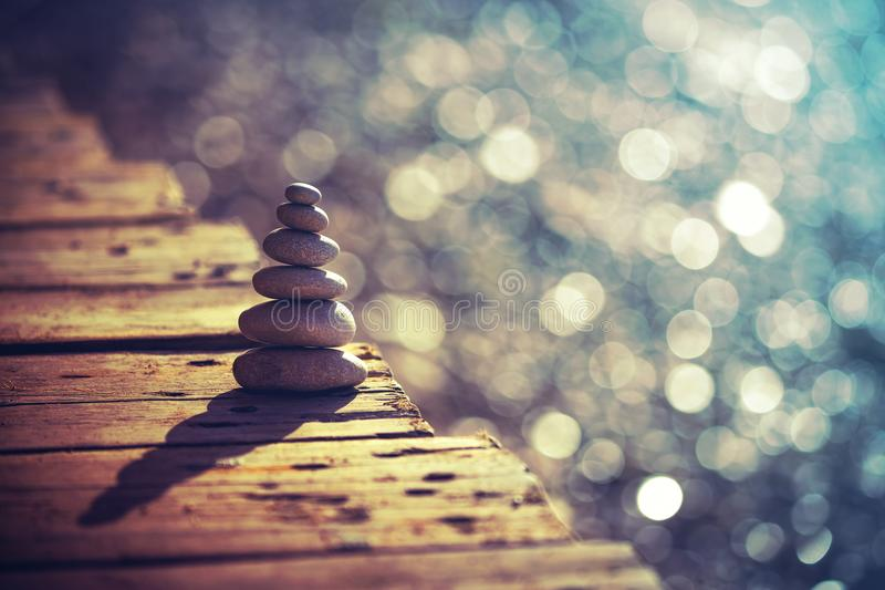 Inner peace and life in balance concept. Inner peace and balance, pile of pebbles on the wooden bridge on the beach, summer vacation on the spa resort, life and royalty free stock images