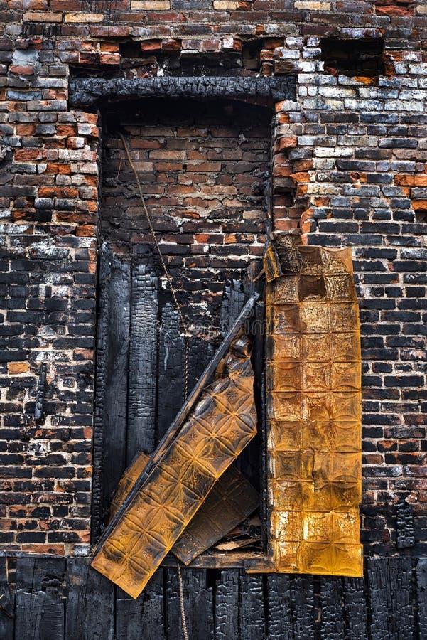 Innere des alten Ziegelgebäudes in der Stadt, verbrannt durch feuerverbrannte Ziegelsteine und rostetes Metall lizenzfreies stockbild