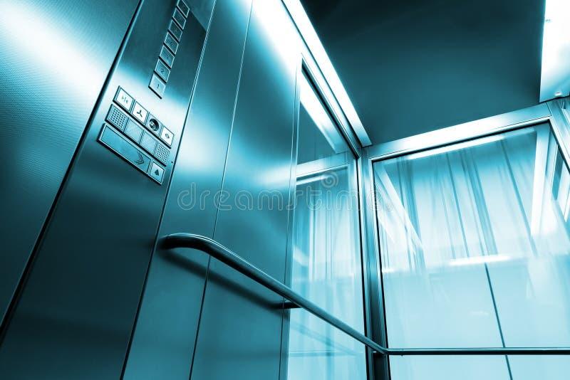 Innerer Metall- und Glas Aufzug im modernen Gebäude, in den glänzenden Knöpfen und in den Geländern lizenzfreie stockbilder