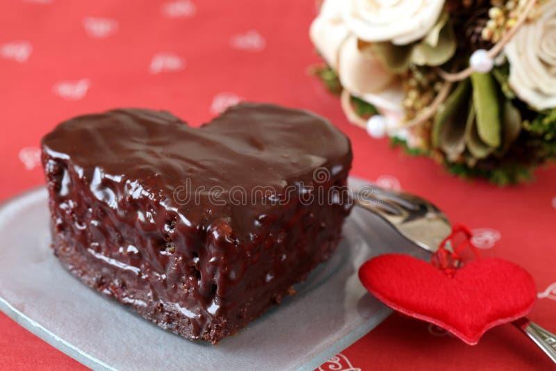 Inneres geformter Schokoladenkuchen und ein Blumenstrauß lizenzfreie stockfotografie