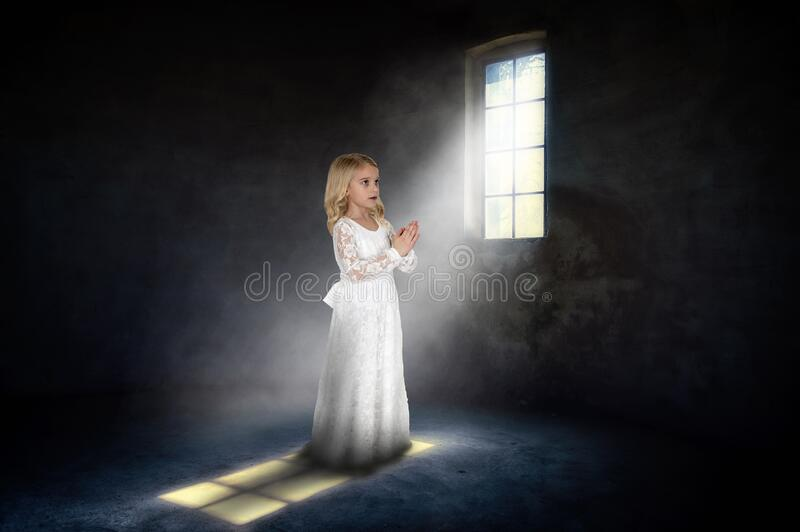 Innocence, Religion, Spiritual, Purity, Praying, Young Girl. Innocent young girl is praying in a dark dungeon room. Abstract concept for spiritual rebirth royalty free stock images