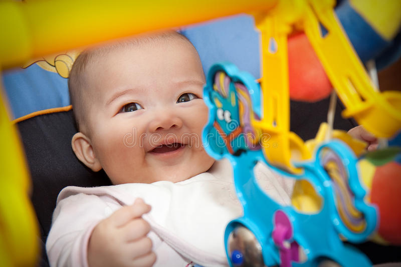 Innocent Colorful smile. Angel`s smile seating in baby seat and surrounded by colorful toys