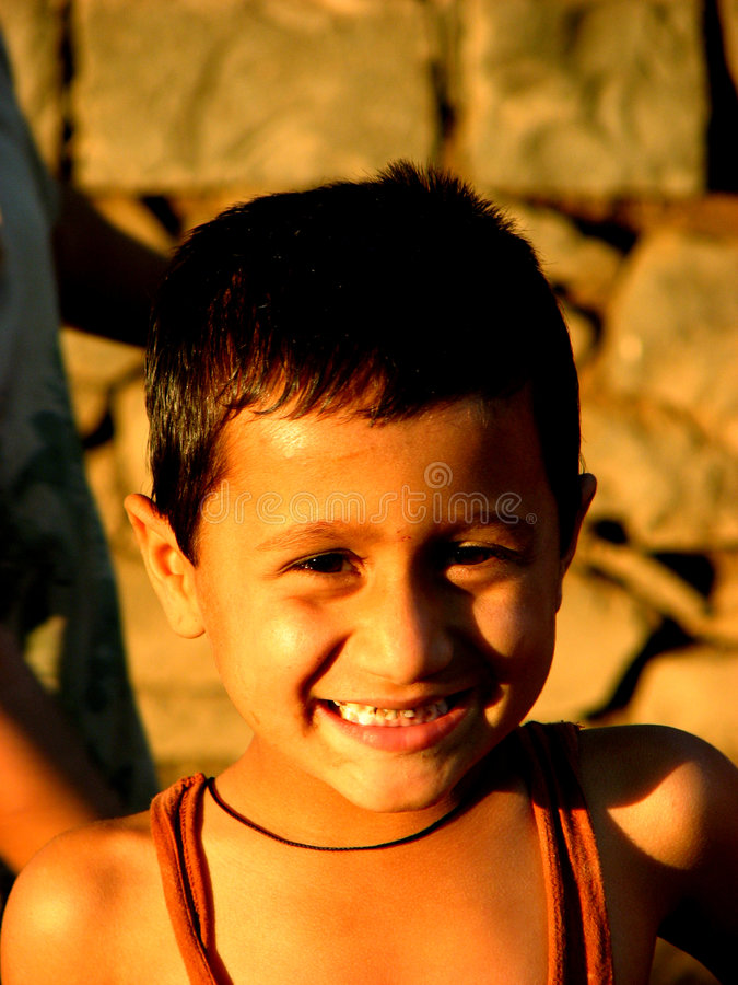 Innocent Gestures. An Indian village boy smiles innocently for the camera stock images