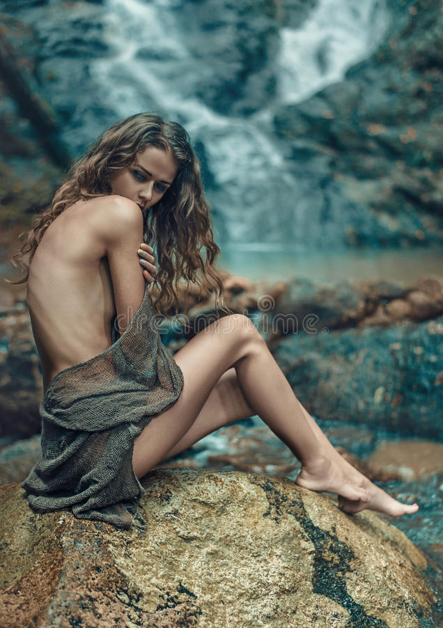 Innocent lady resting on the sharp rock royalty free stock photos