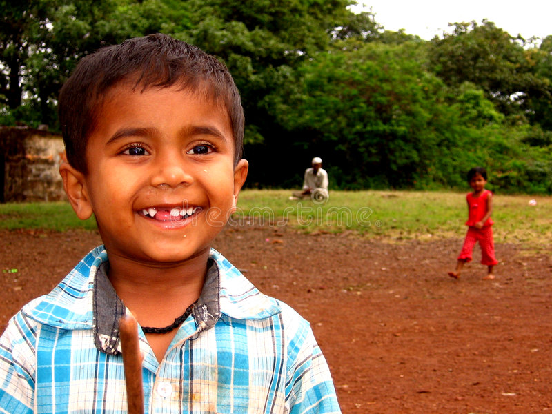 Innocent Smile. A poor boy from India smiles innocently stock photo