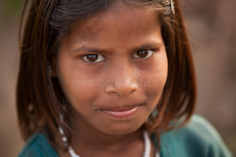 Innocent smile of indian female child. Poor, dirty, rough skin but bright eyes stock image