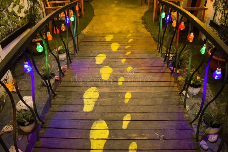 Innovatief idee van menselijke voetsporen op de houten weg die met kleurrijke lichten op het traliewerk hangen Aantrekkelijke ver stock afbeelding